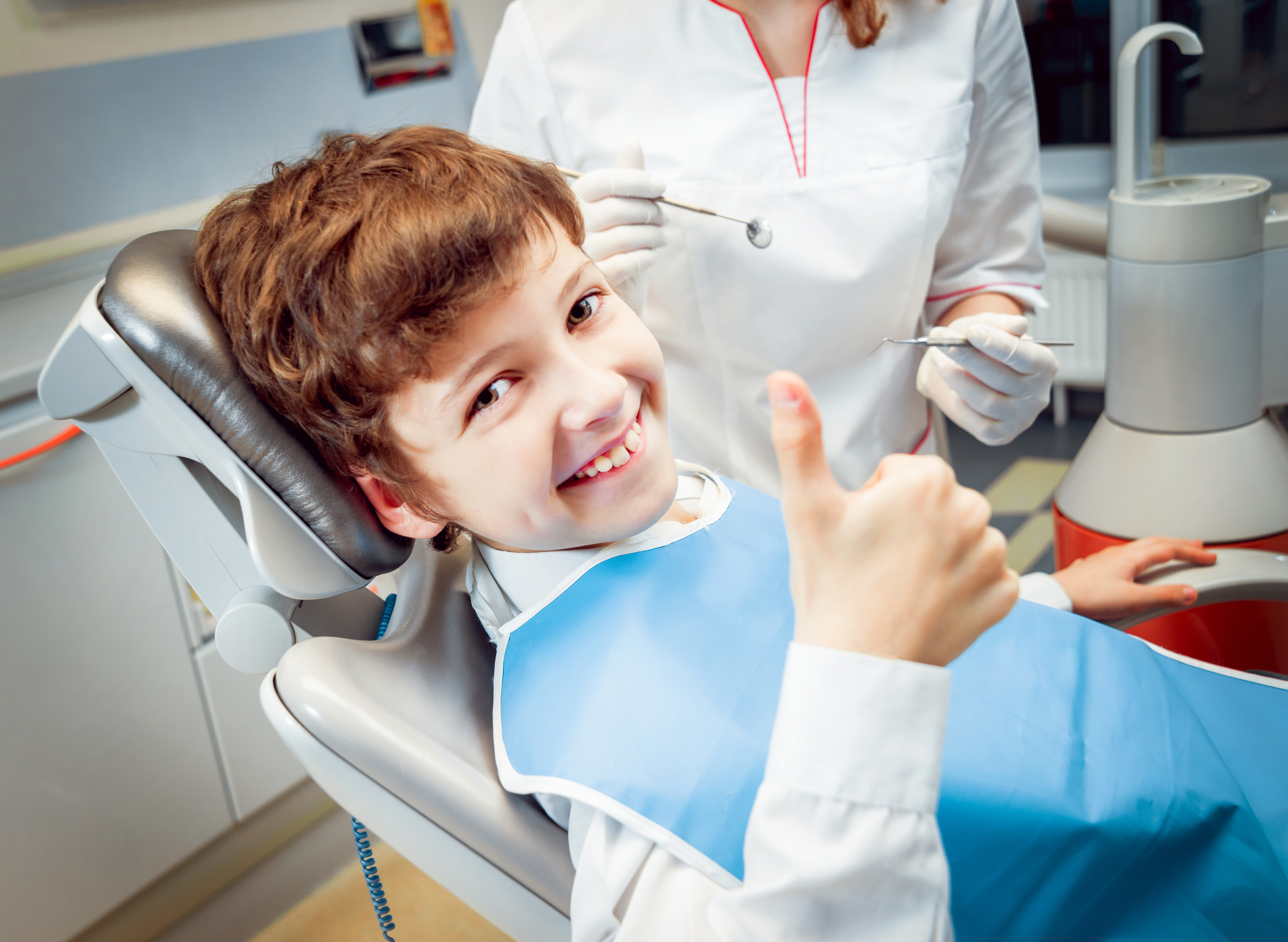 Child giving thumbs up in dentist chair